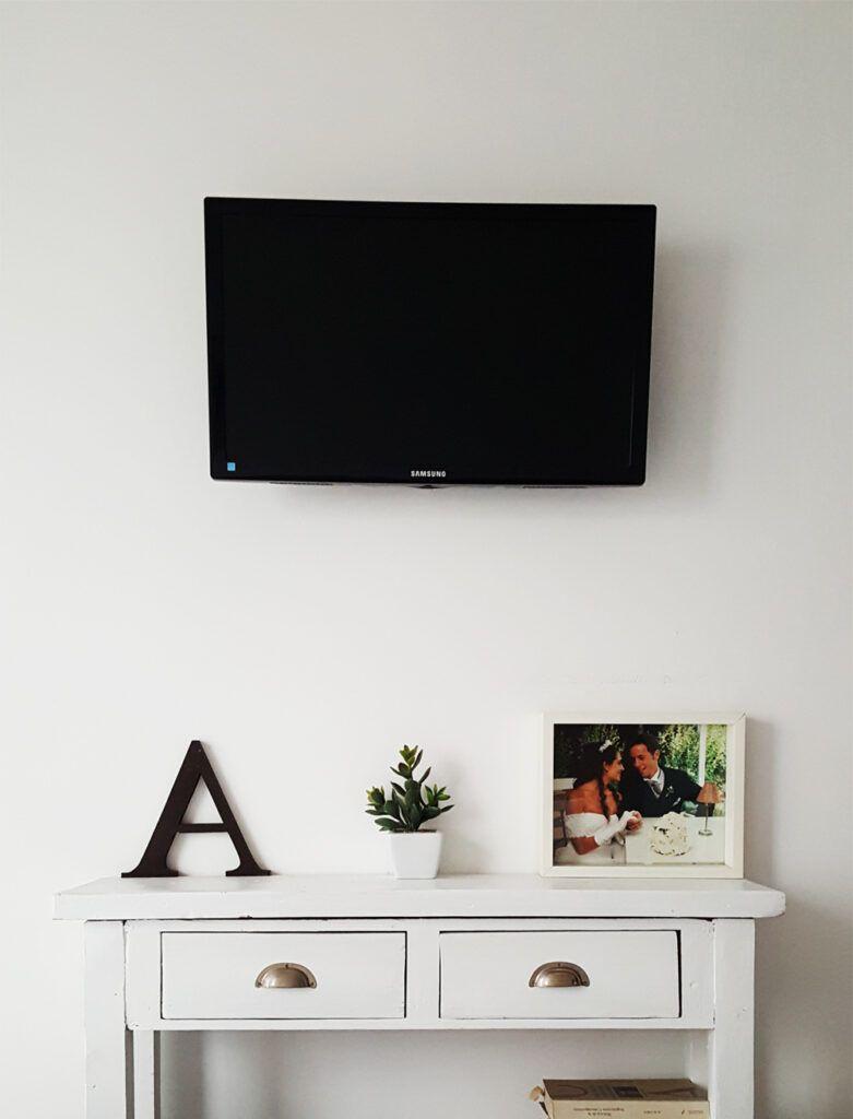 Un mueble de apoyo angosto que acompañe a la tv. Si es del color de la pared es mucho mejor asi pasa desapercibido